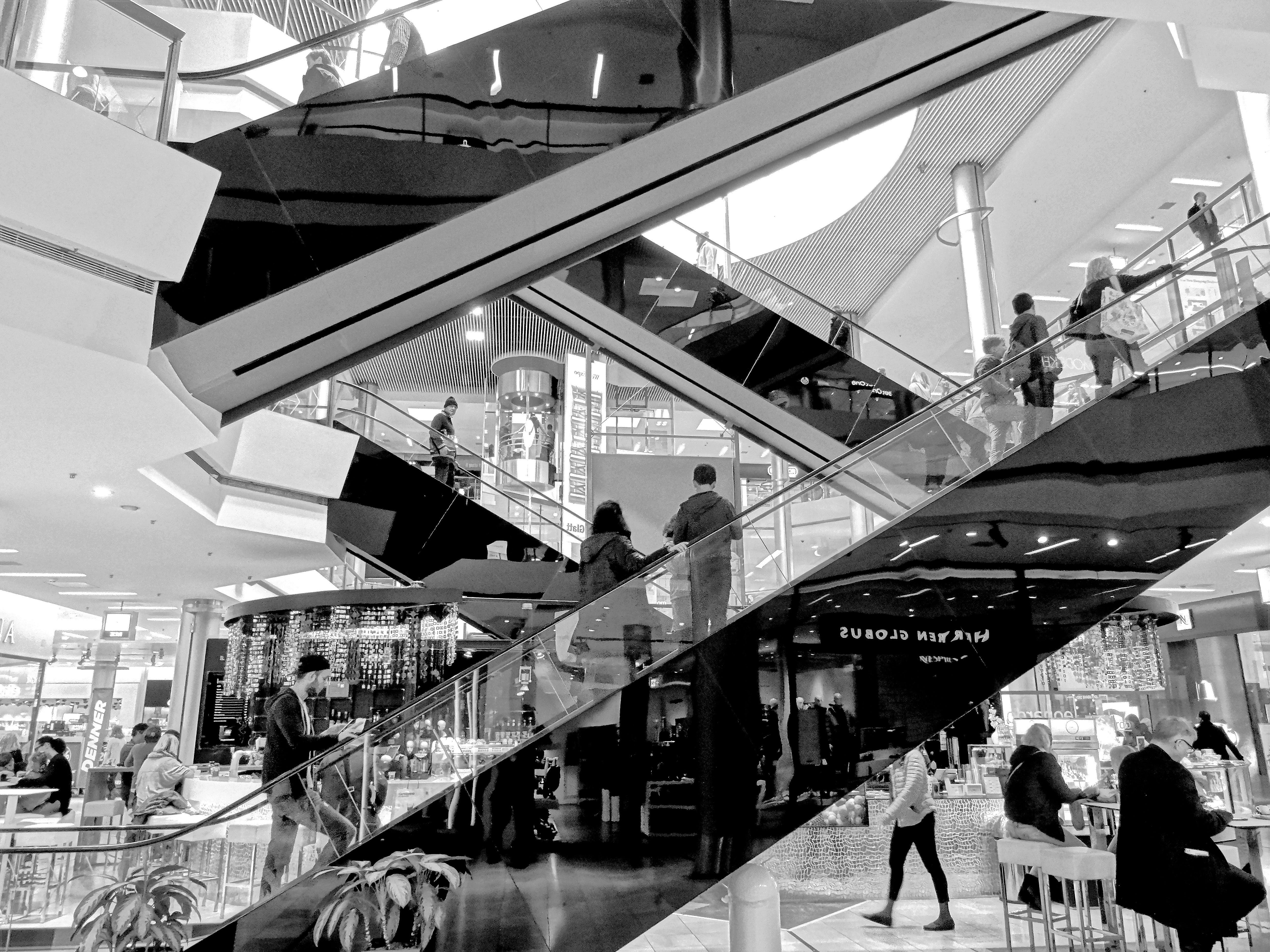 Grayscale Photography of People Standing on Escalator