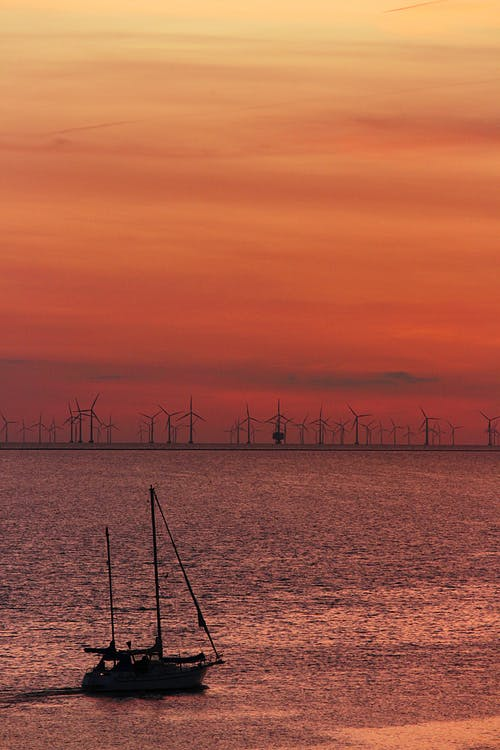 Sailboat on calm lake with modern windmills on shore at sundown