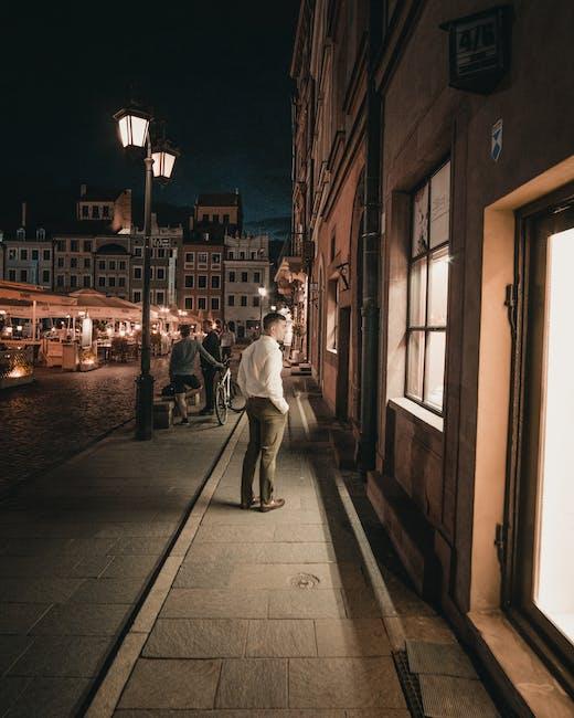 Man in white shirt and brown pants walking on sidewalk during night time