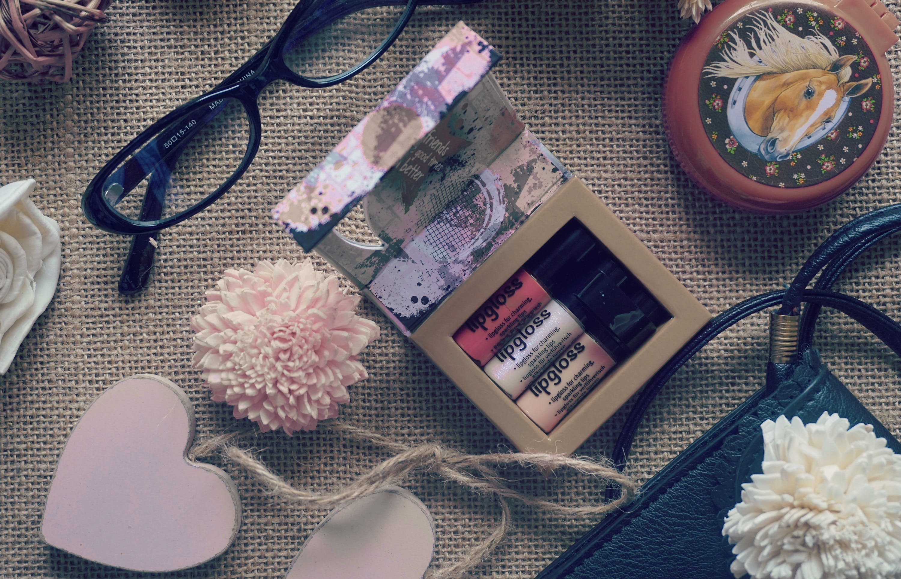 Flat Lay Photography of Lipstick , Eyeglasses and Heart Hanging Decor