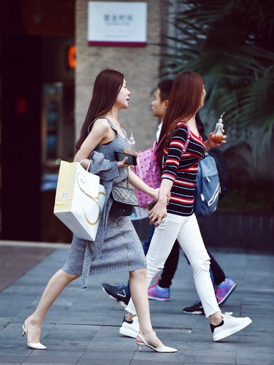 Two Women Holding Glass Bottles Standing Near Brown Wall
