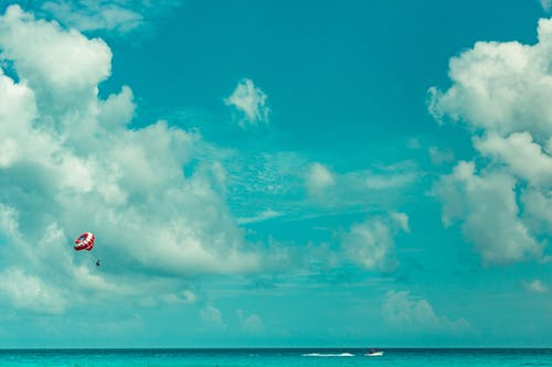 Person Parasailing Under White Clouds and Blue Sky