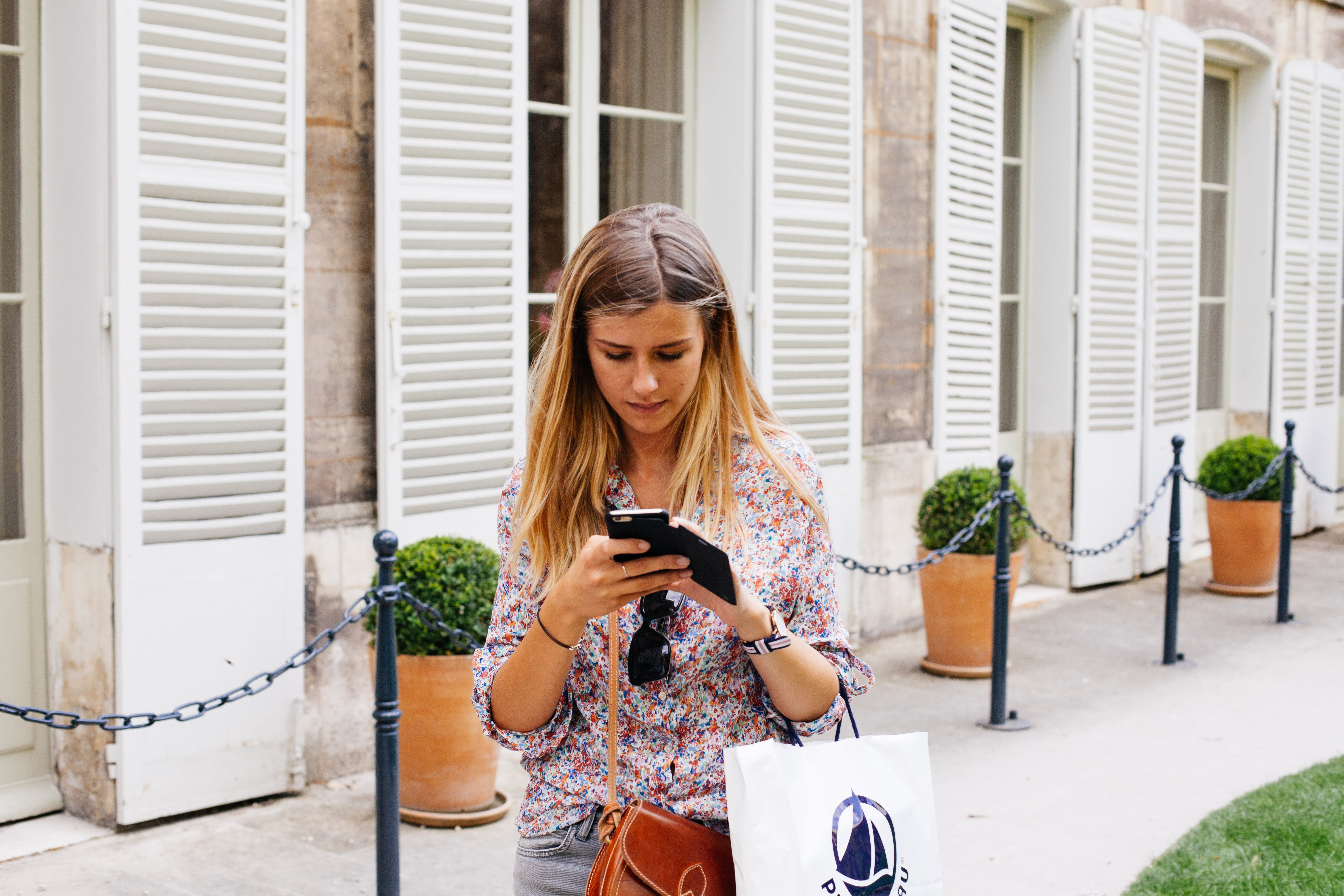 Woman Holding Smartphone Near Building