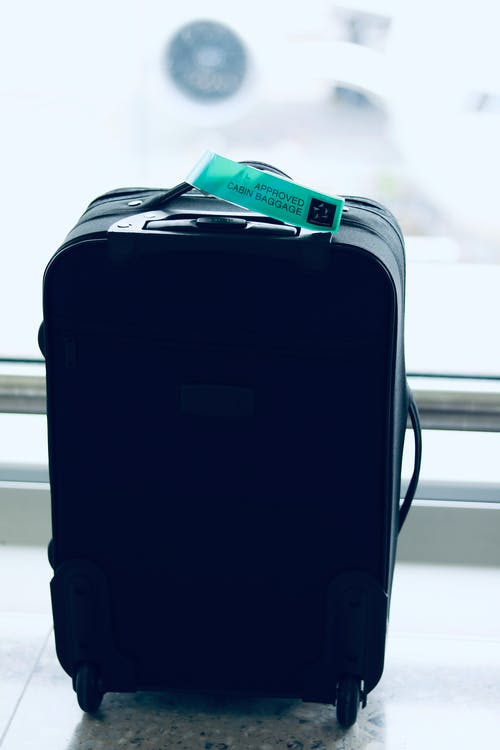 Black Luggage Bag Near Wall