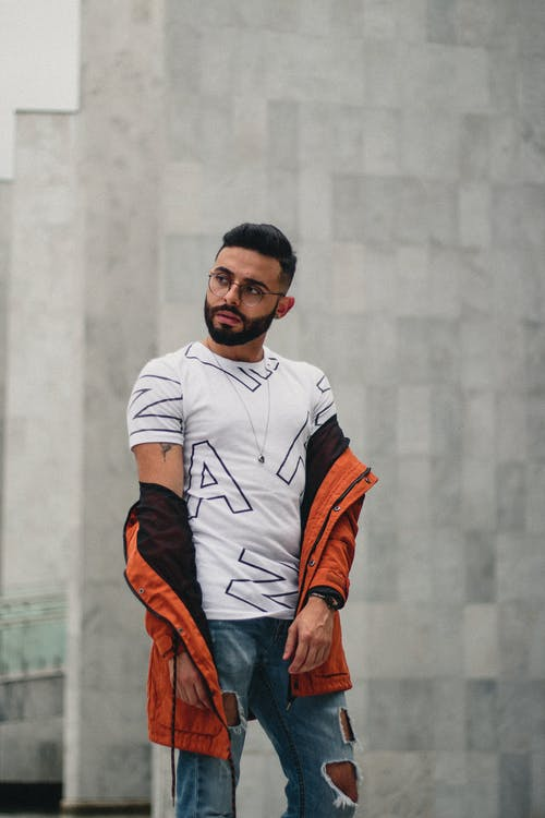 Photo of Man in White T-shirt, Orange Jacket, and Blue Jeans Posing In Front of Gray Wall