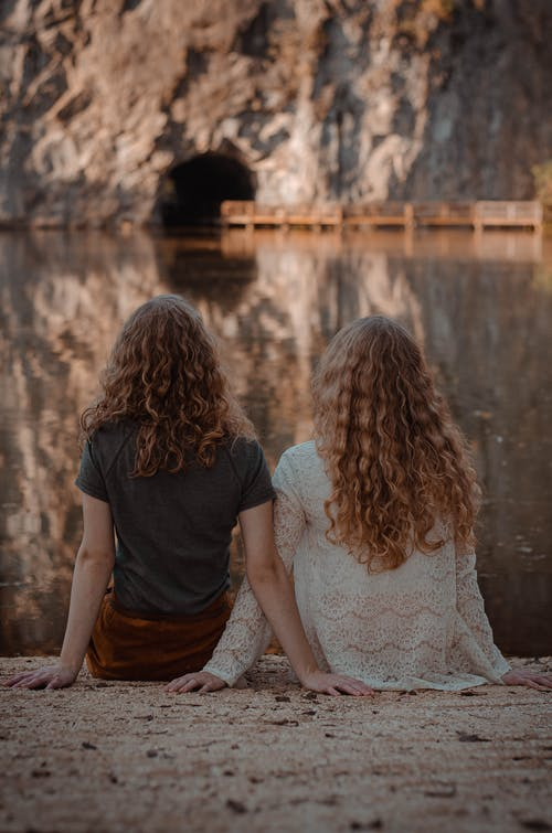 Photography of Two Women Sitting on Ground Facing on Body of Water