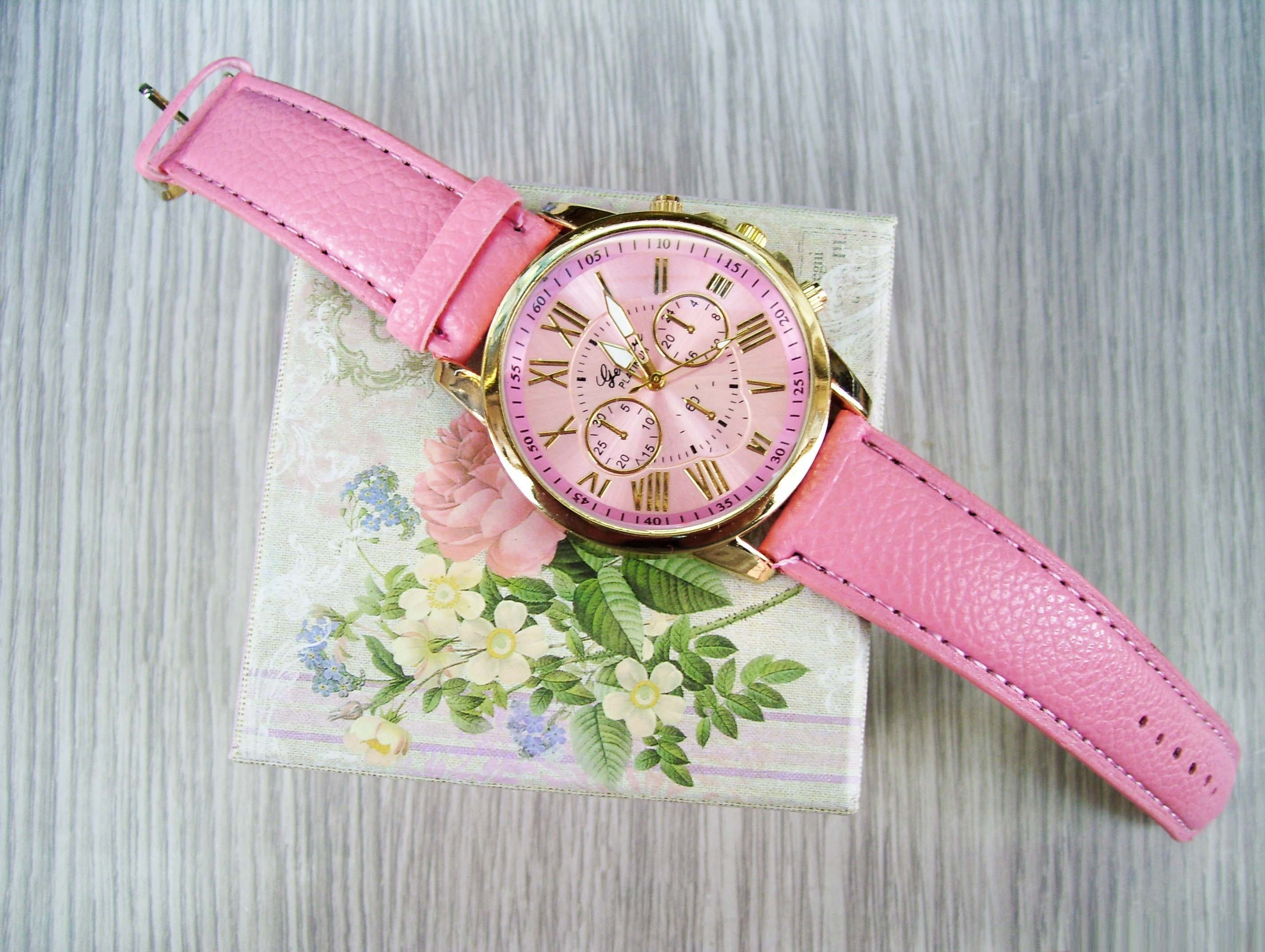 Round Gold-colored Chronograph Watch With Pink Leather Strap on Box