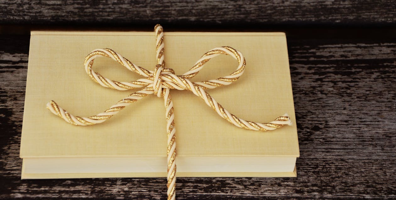Book Tied With Rope on Black Wooden Surface