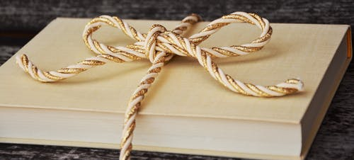 Closeup Photography of Ribbon Tied Book