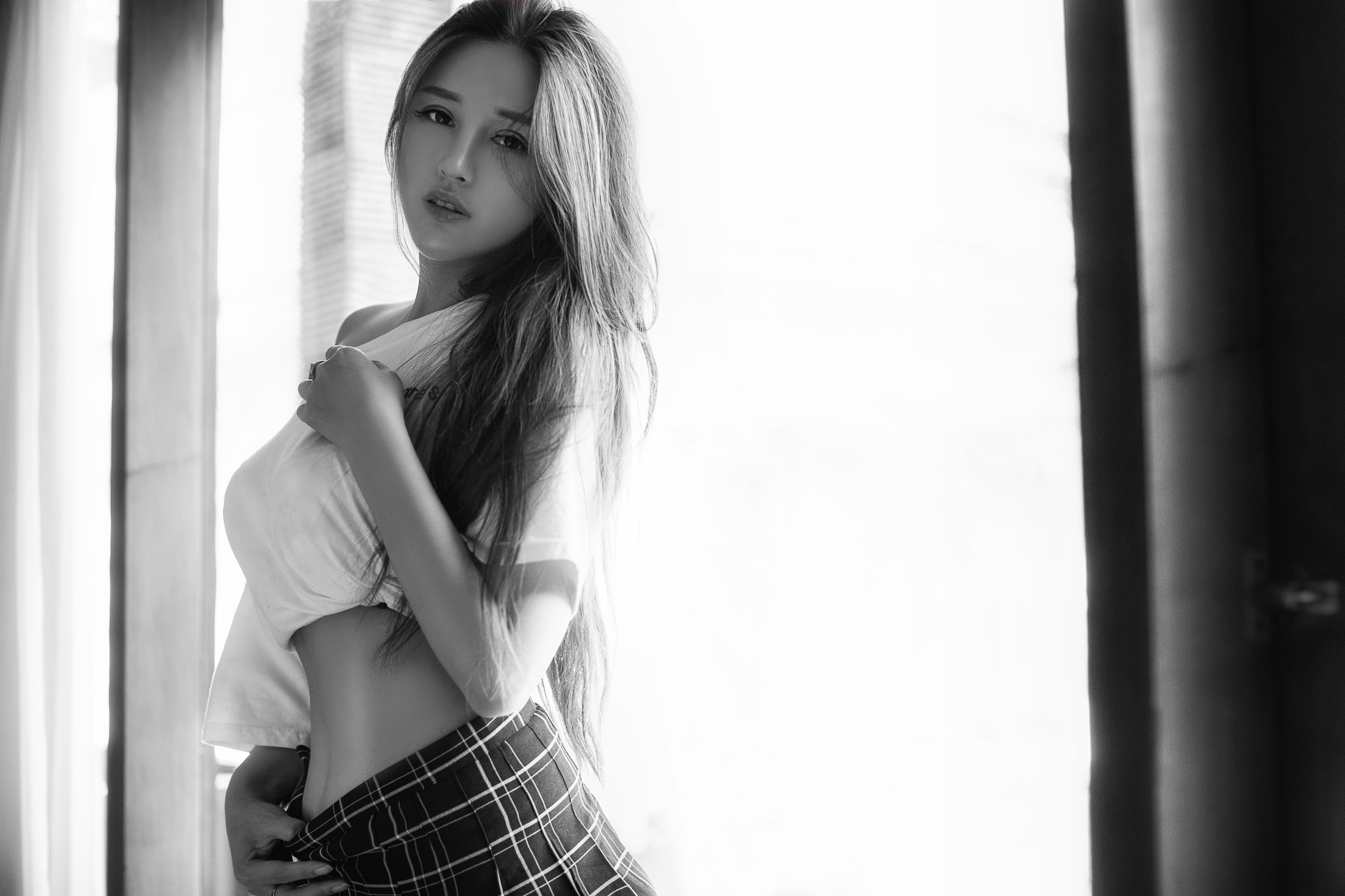 Gray scale photography of a woman wearing white crop top