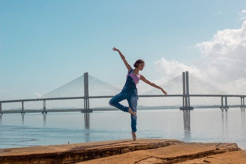 Photo of woman standing on rock formation doing yoga