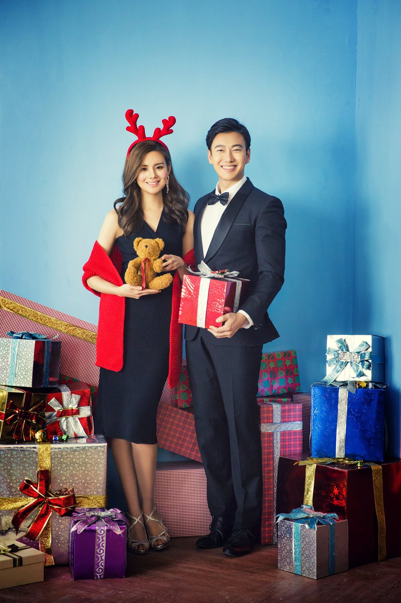 Two Woman and Man Standing Beside Wall With Gift Boxes