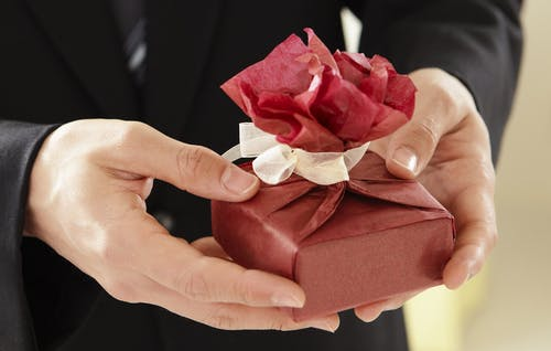 Person Holding Box With Red Wrapper