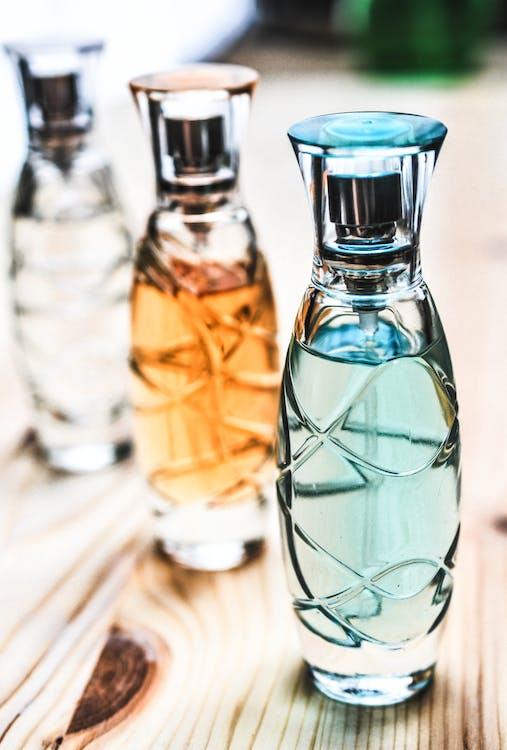 棕色木製表面上的三個什錦透明玻璃香水噴霧瓶