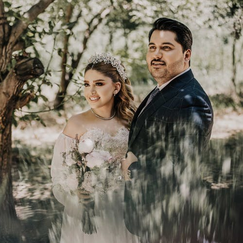 Newly Wed Couple Standing Under Trees