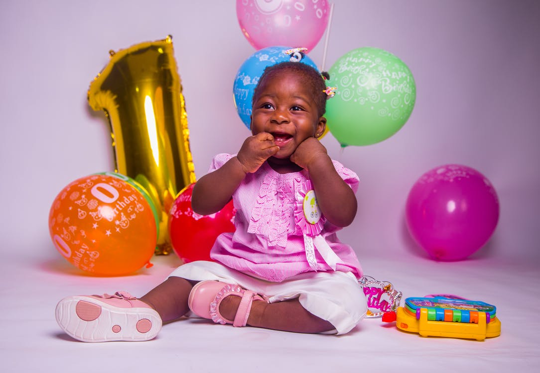 Photo of baby girl sitting on floor with balloons