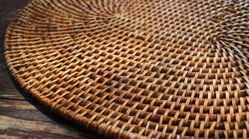 Round Wicker Board on Wooden Surface