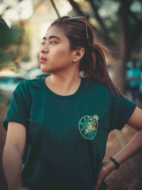 Selective Focus Photo of Woman in Green T-shirt Posing While Looking to Her Right