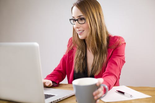 Woman Using Laptop While Holding Mug