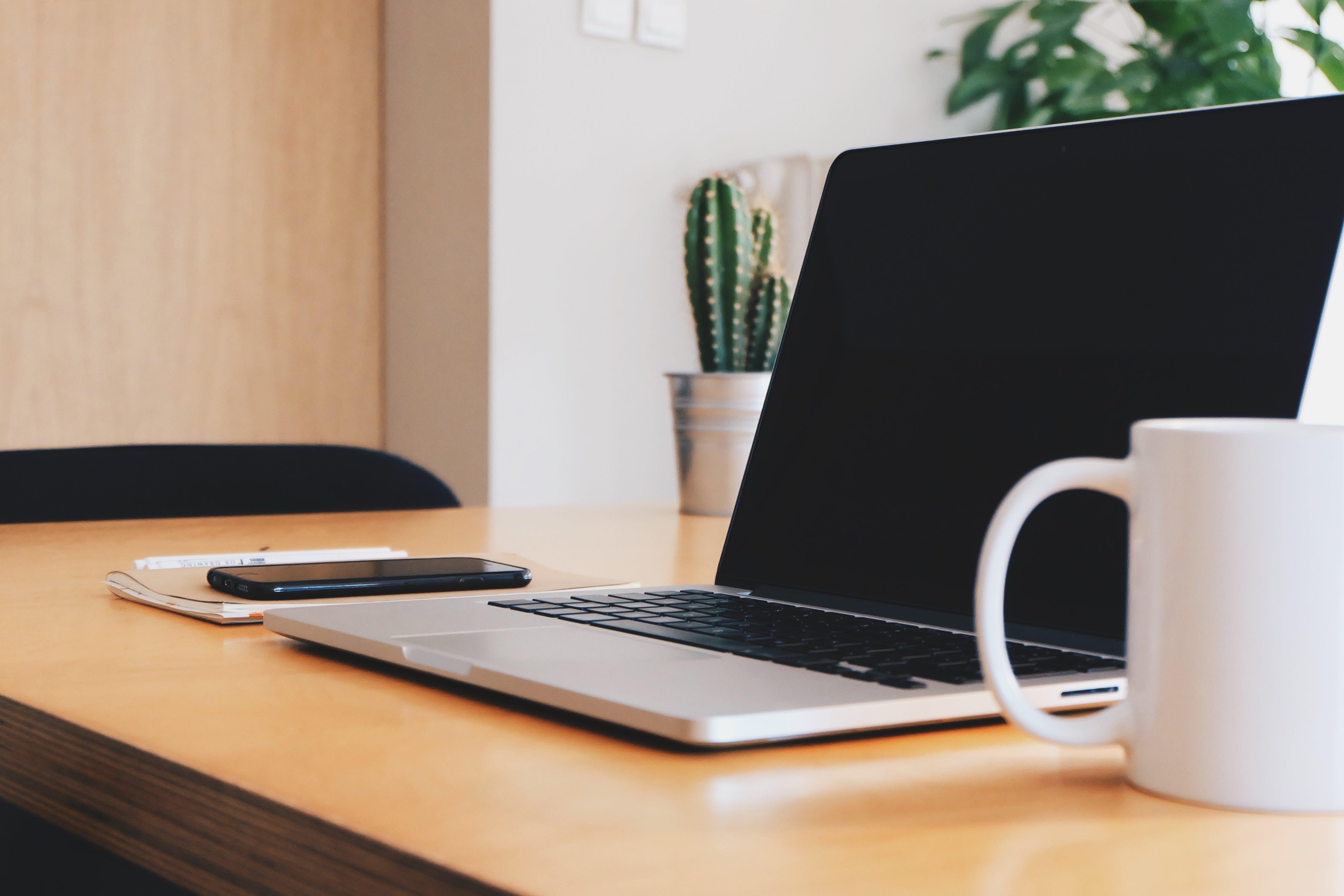 Macbook Pro on Tabletop Beside Mug