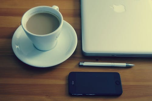 Cup and Saucer Beside Macbook, Pen, and Iphone