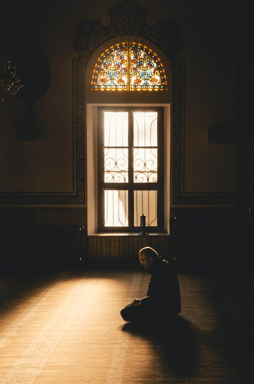 Photo Of Man Kneeling While Praying