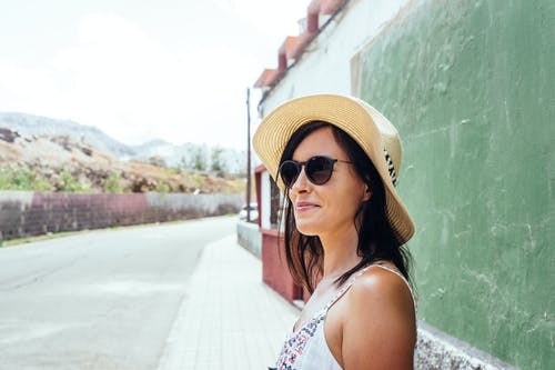 Close-up Photo of Smiling Woman in Sunglasses and Sun Hat Standing on Sidewalk In Front of Green Wall
