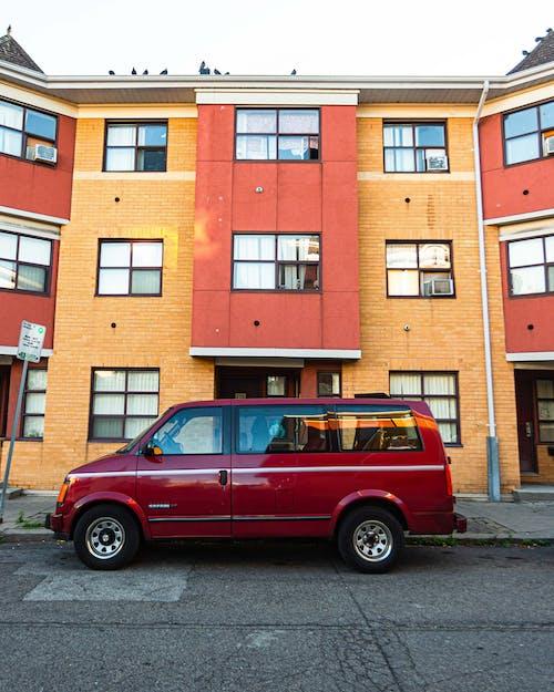 Red Van Parked on Curb Beside Building