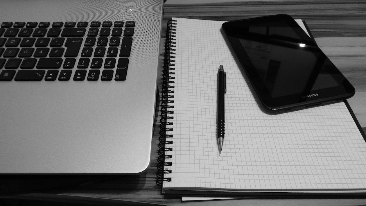 Smartphone Displaying Black Screen Beside Retractable Pen on Grid Notebook