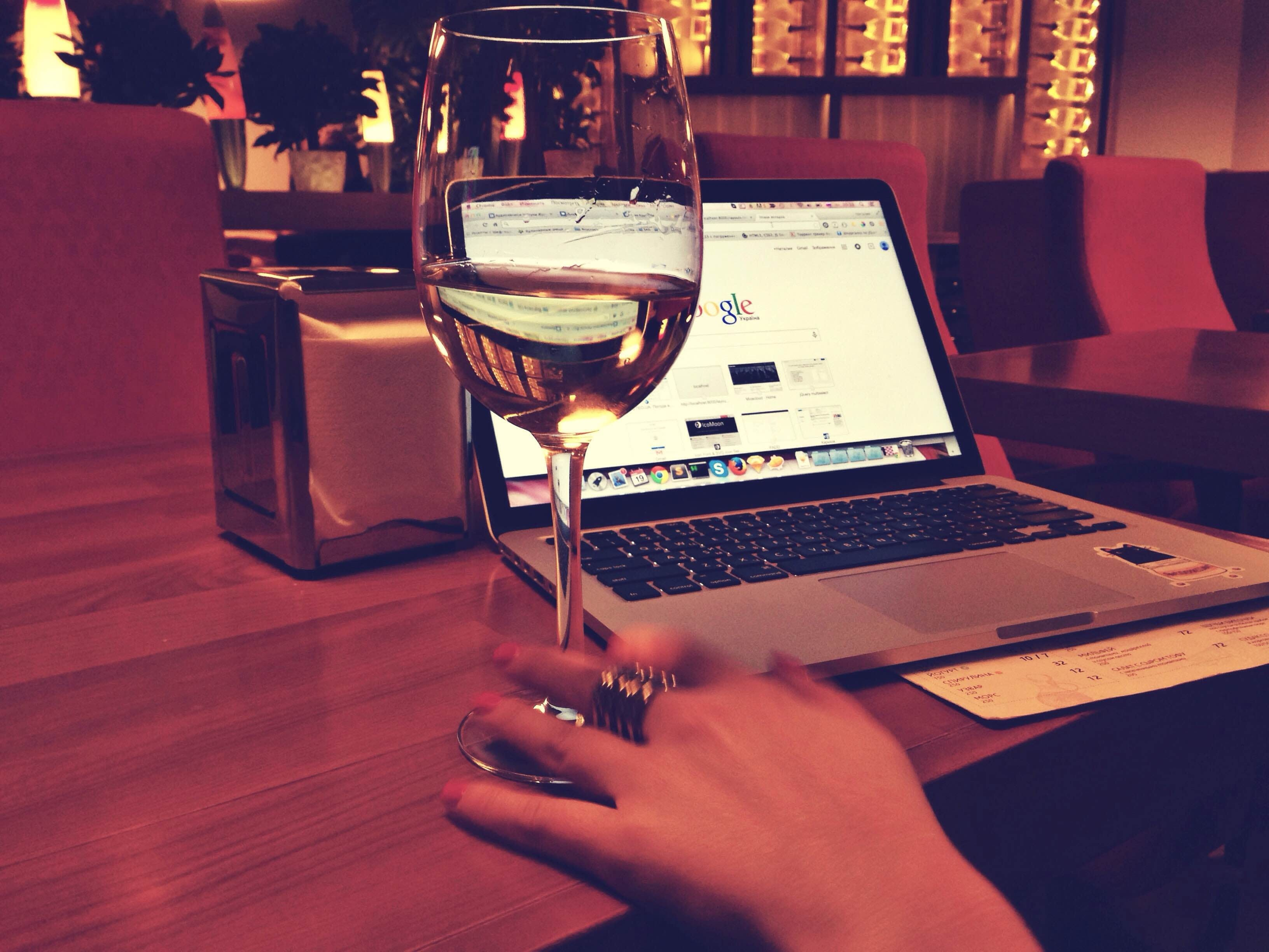 Person Using Macbook Pro Near Wine Glass on Table