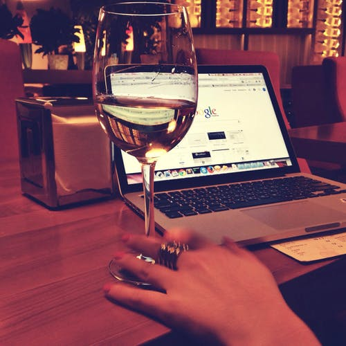 Person Using Macbook Pro Near Wine Gl On Table