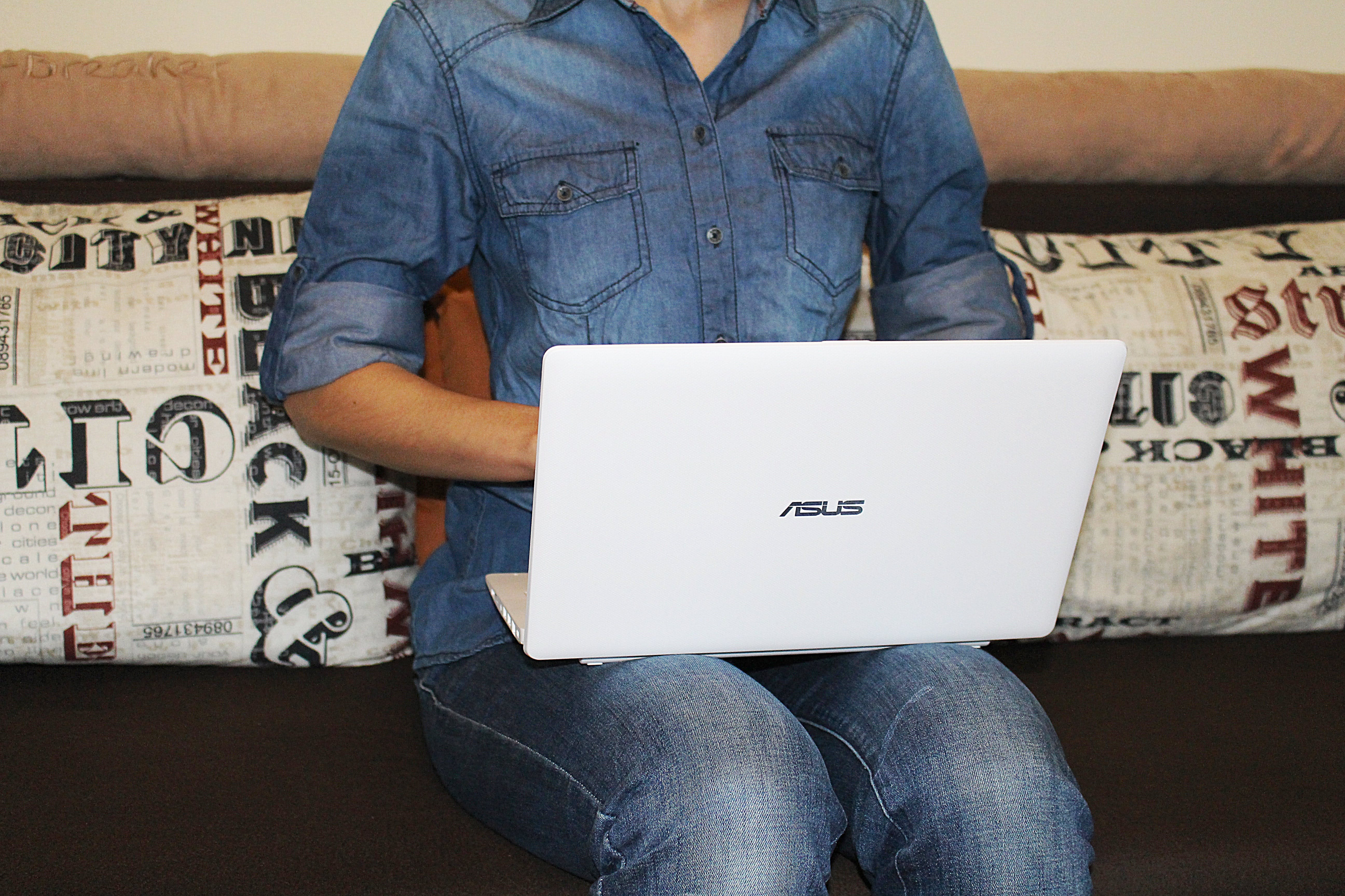 Person in Blue Dress Shirt Sitting on Couch While Using White Asus Laptop