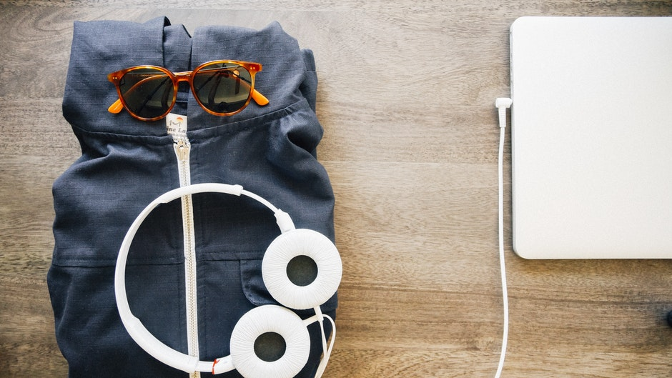 Image of a canvas holdall that has been packed and has headphones and sunglasses on it