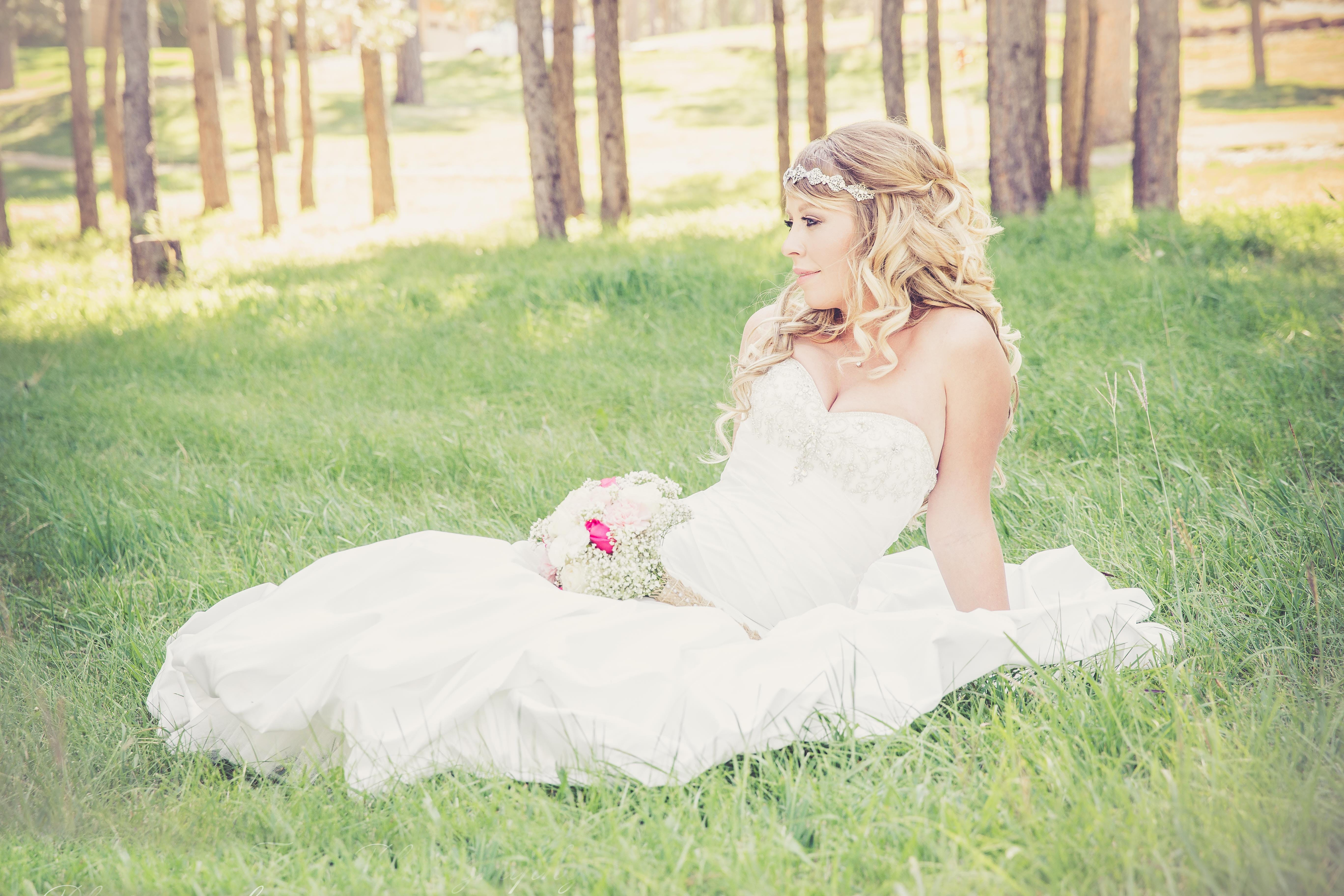 Woman in White Bridal Gown on Green Grass
