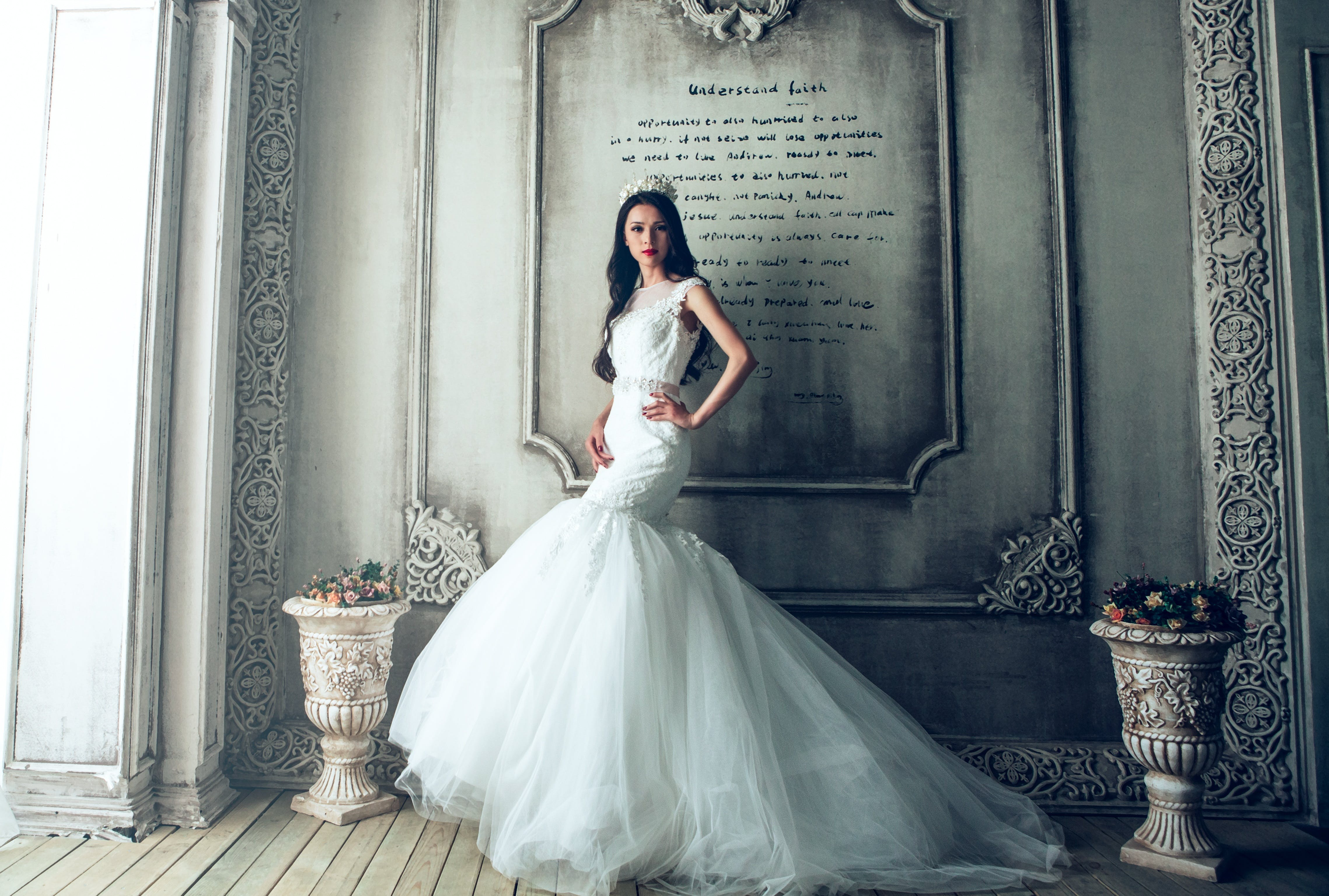 Woman Wearing White Wedding Gown Standing Beside Gray-painted Wall