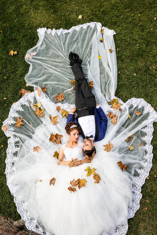 Aerial Photo of Man and Woman Lying on Grass Field, wedding, bride and groom