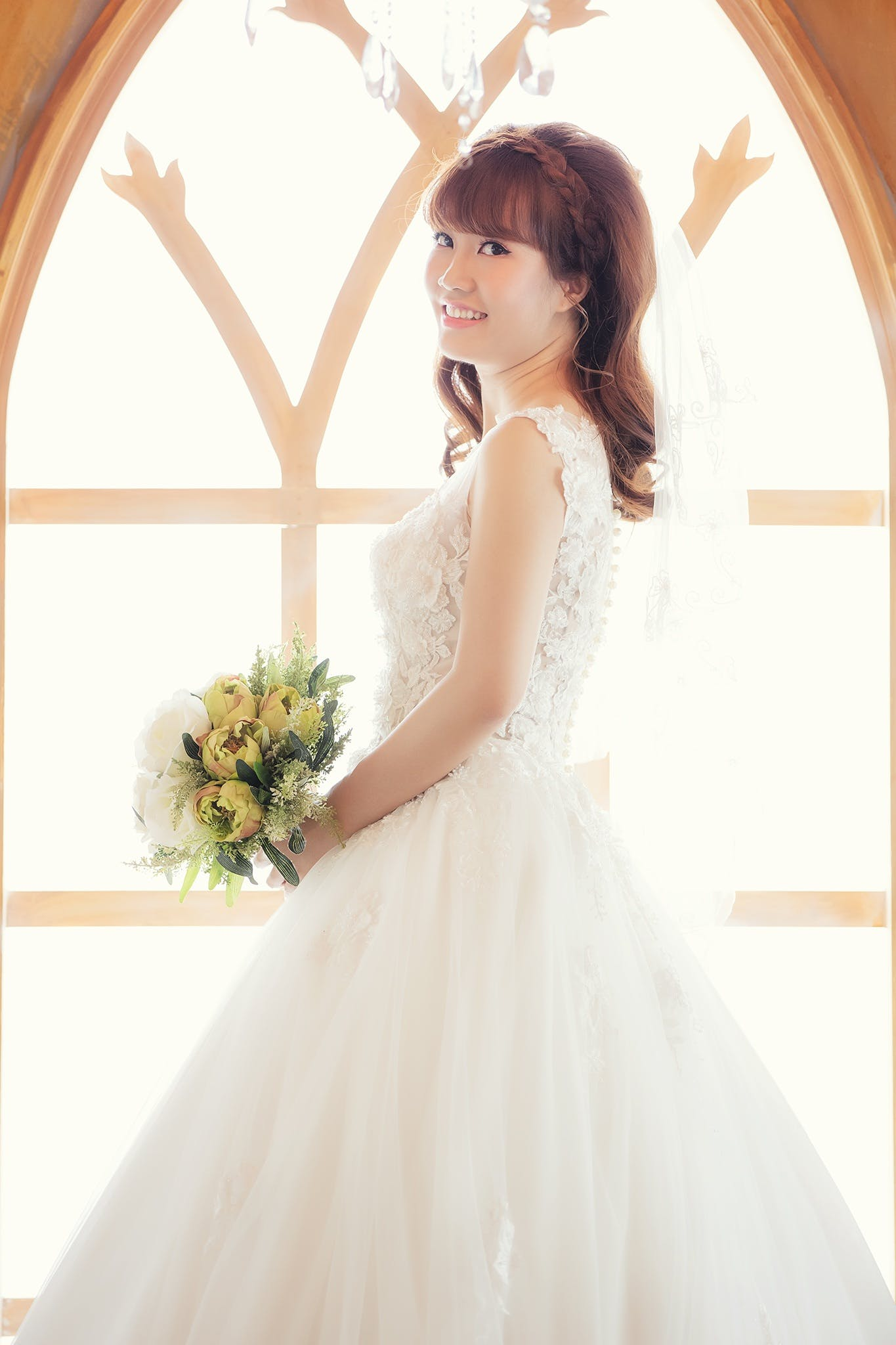 Woman Wearing White Wedding Gown Holding Bouquet of Yellow Flowers