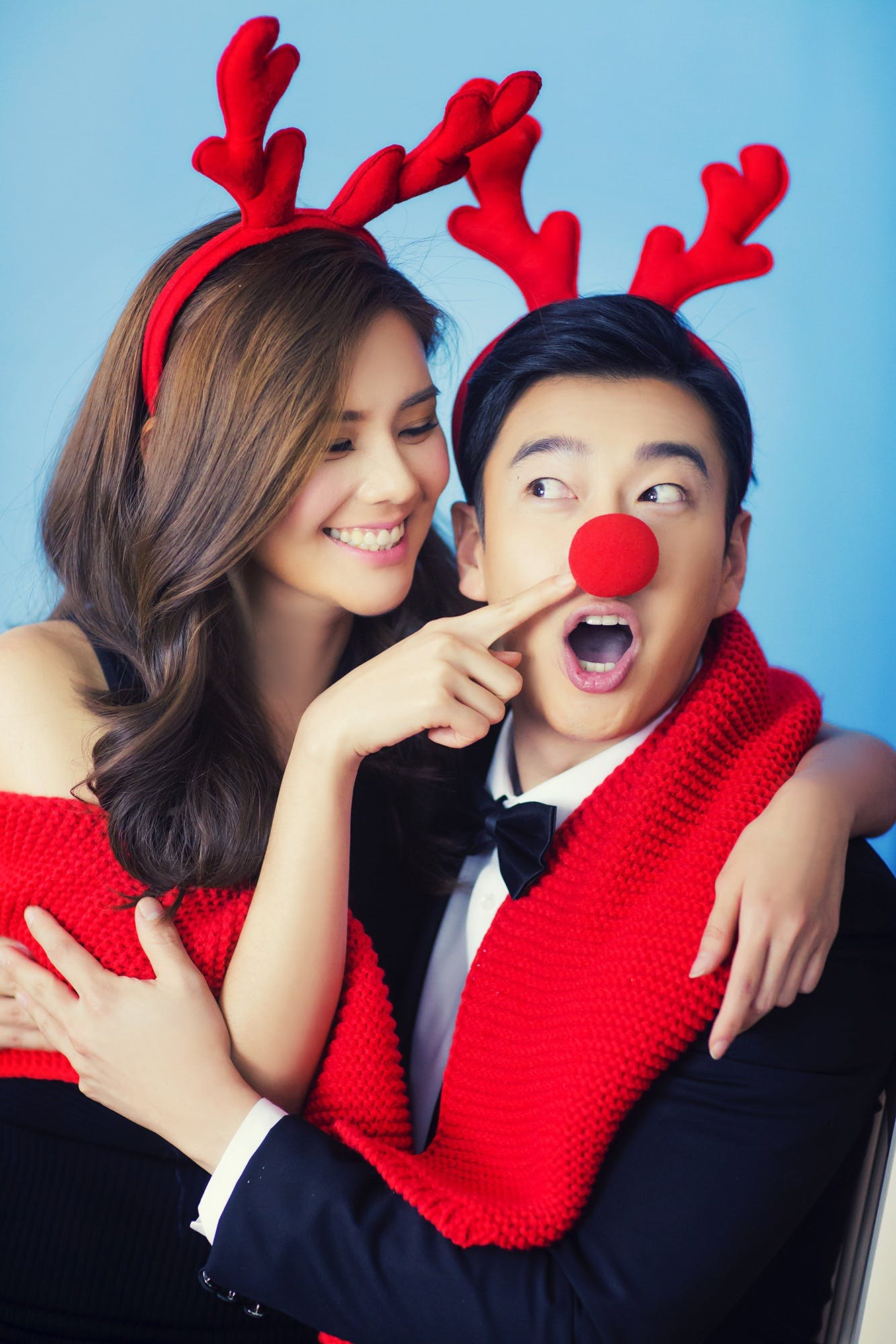 Woman Pin Pointing Man's Red Reindeer Nose