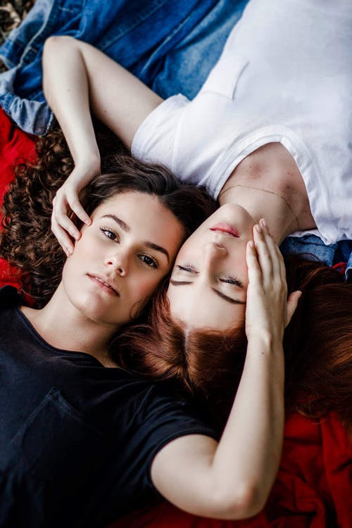 Two Women Lying On Red And Blue Blanket