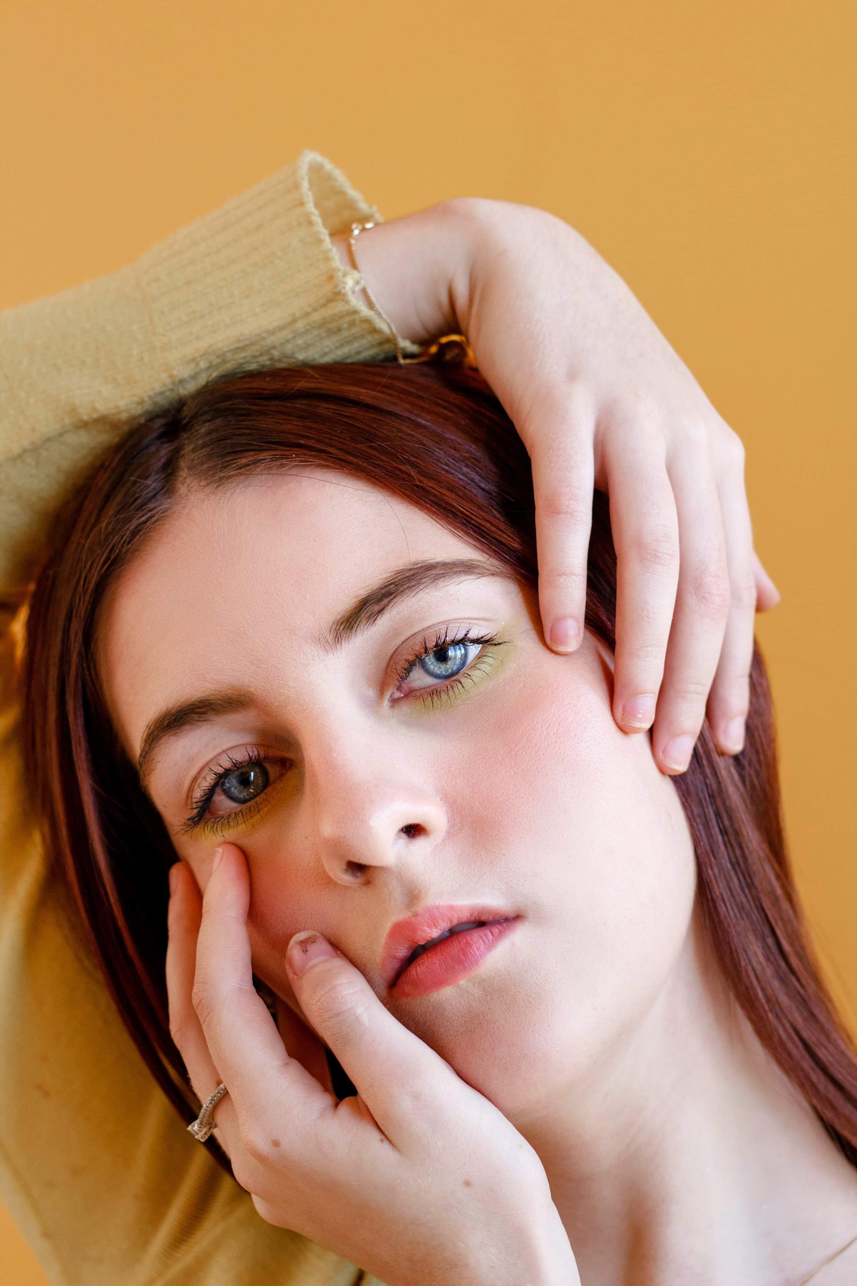 Close-up Photo of Woman Posing With Hands on Her Head In Front of Yellow Background