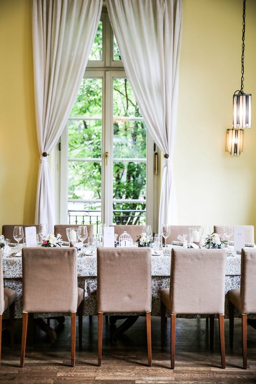 Gray Padded Chairs With Wooden Bases Aligned Beside Table Near Window