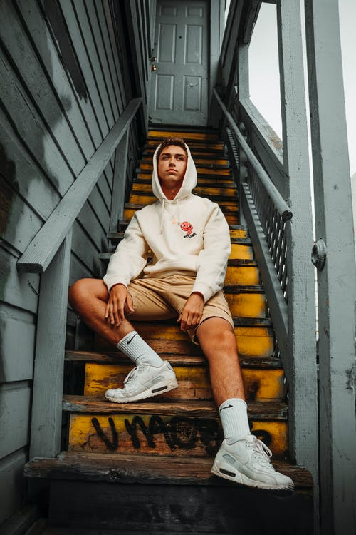Low-Angle Photo of Man Wearing Hoodie While Sitting on Stairs