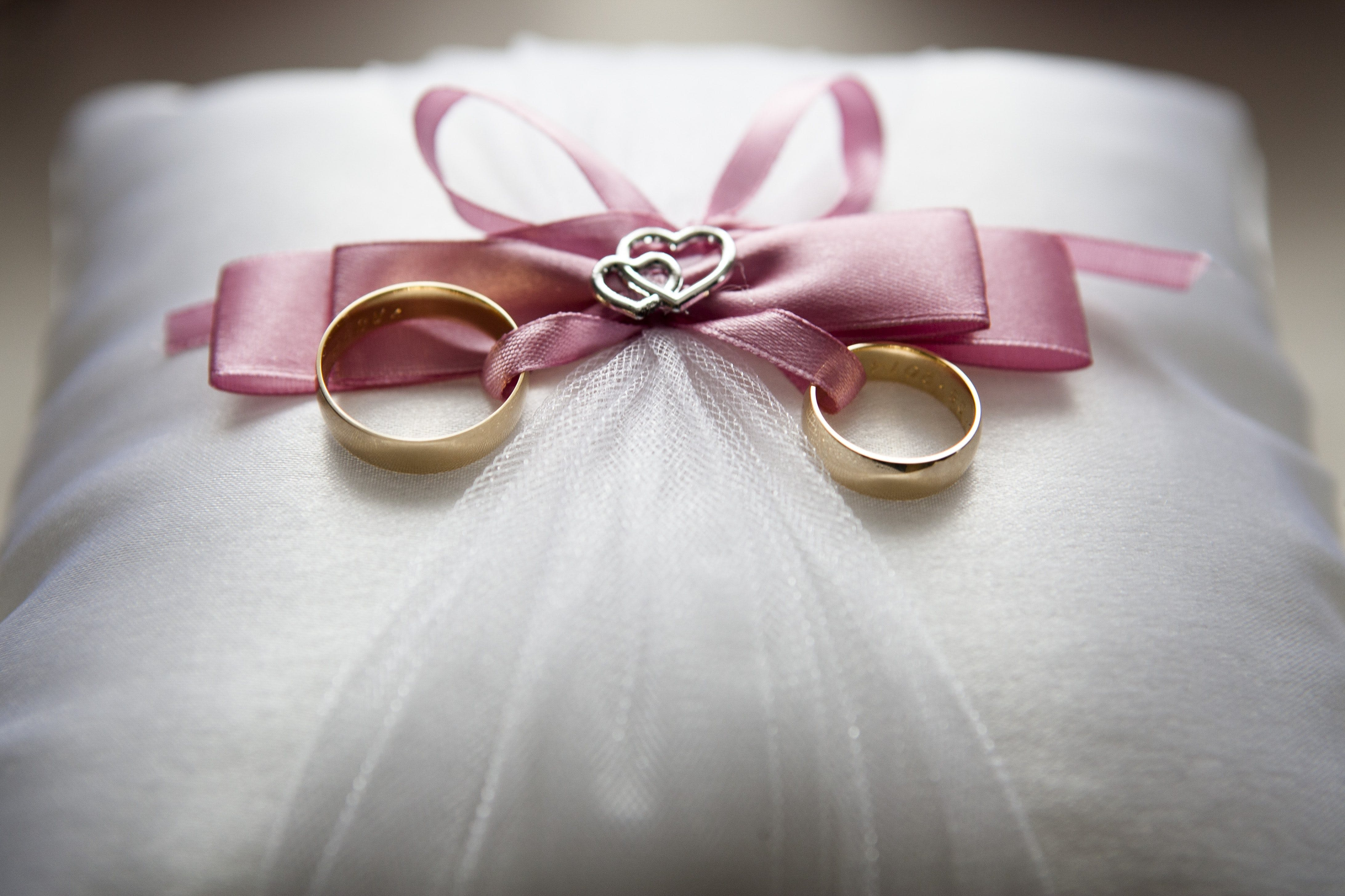 Selective Focus Photography of Silver-colored Engagement Ring Set With Pink Bow Accent on Throw Pillow
