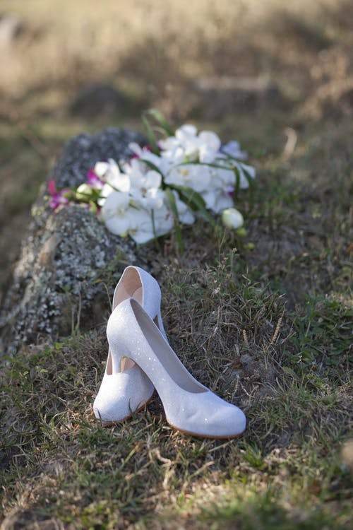 Pair of Heeled Shoes Near Flowers in Grass