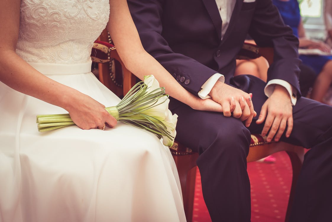 Wedding Couple Sitting on Chair While Holding Hands