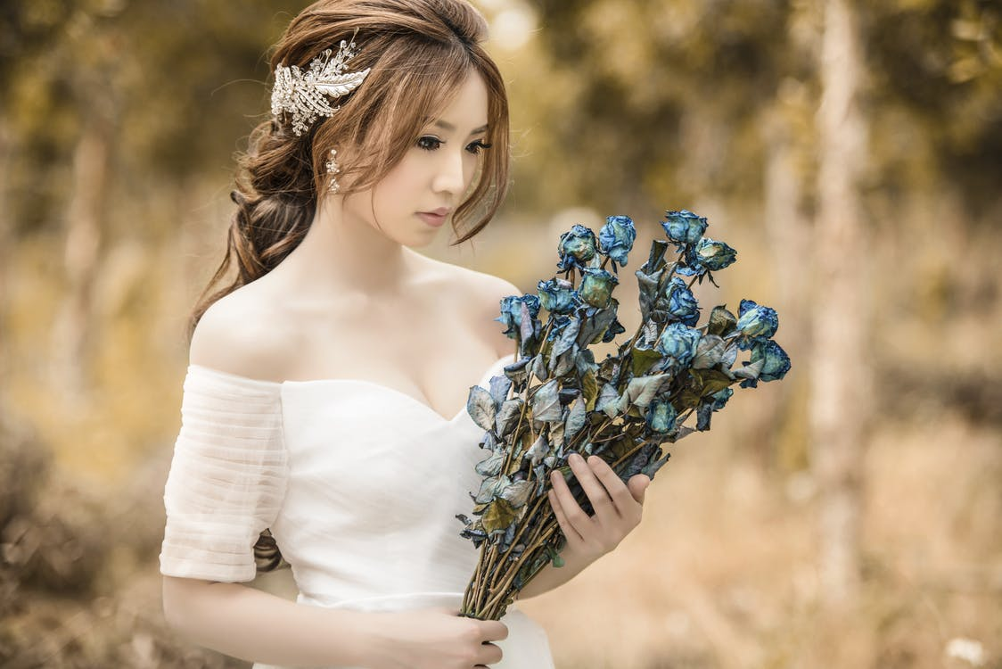 Woman Holding Blue Flowers