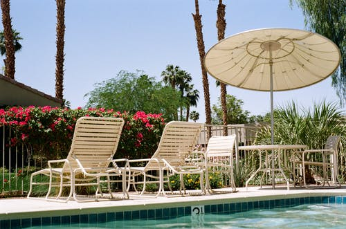 Two White Metal Loungers Beside Pool