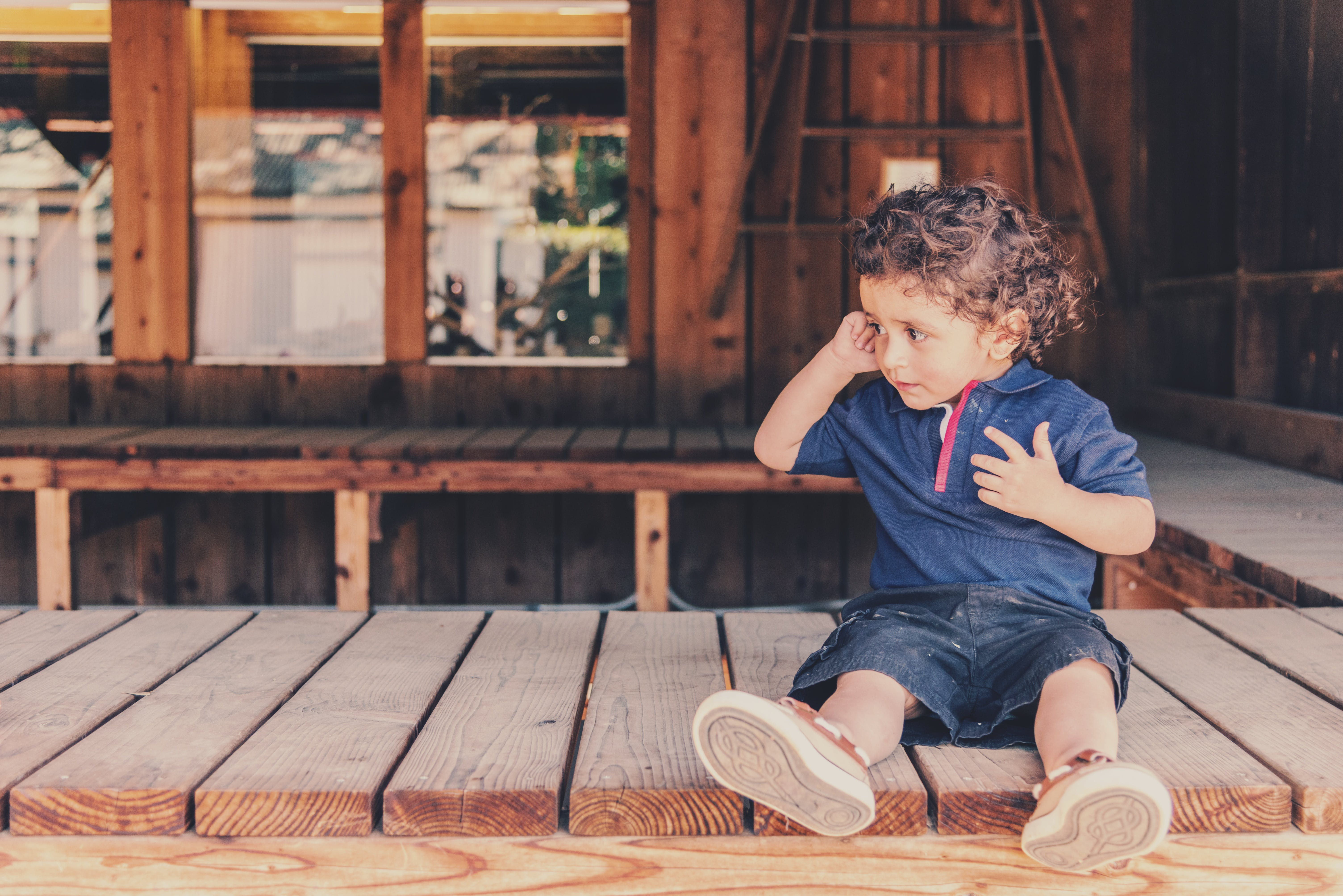 Boy Sitting on Brown Wooden Boat Dock