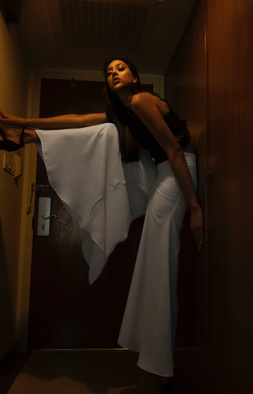 Photo of Woman in Black Top and White Palazzo Pants Standing by Doorway Posing While Leaning on Wall and Her Leg Against Wall