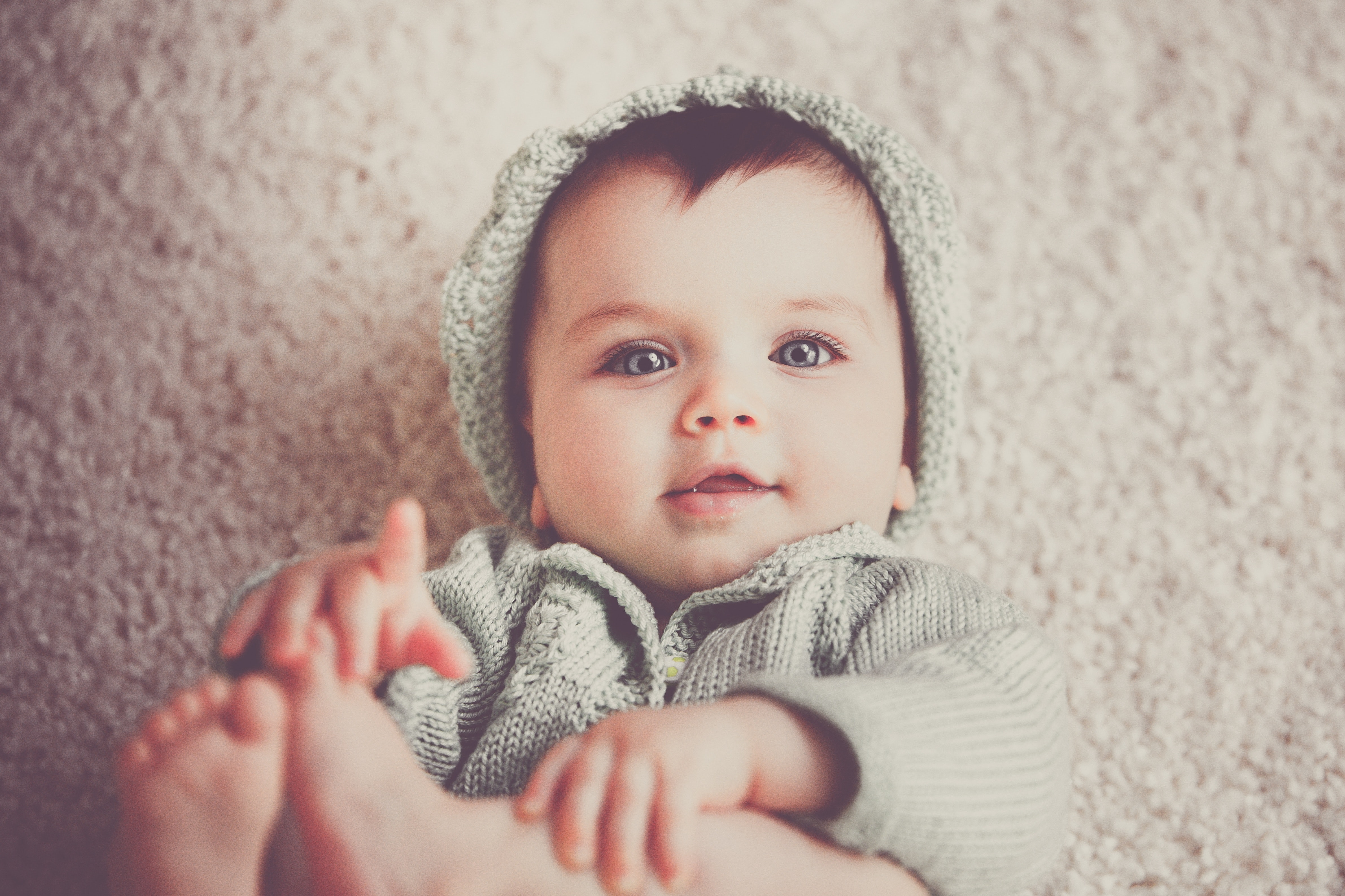 baby on gray knit hooded clothes lying on carpet free stock photo